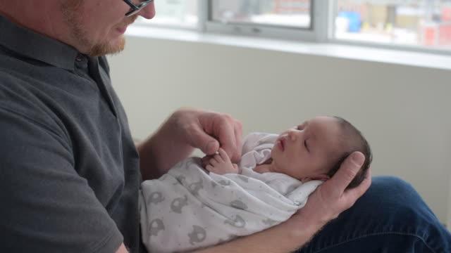 Father holding newborn baby.
