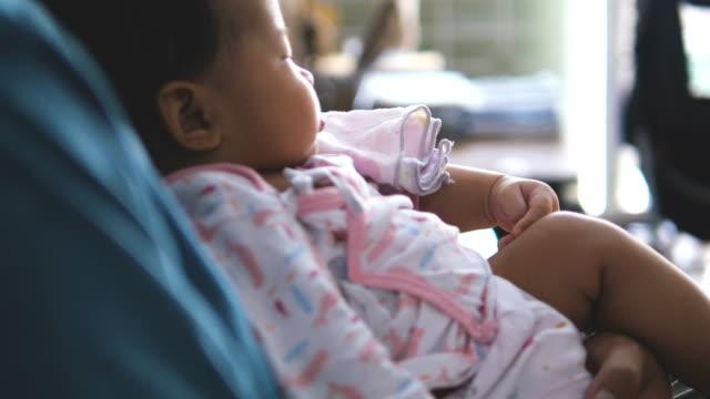 vater holding newborn baby vor dem fernseher - genderblend stock-videos und b-roll-filmmaterial