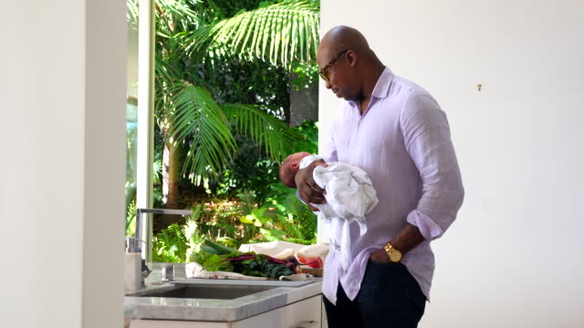 ms father holding newborn son in kitchen - genderblend stock videos & royalty-free footage