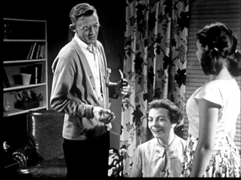 vidéos et rushes de 1953 b/w father holding pipe, and mother talk to adolescent daughter in living room - fille de