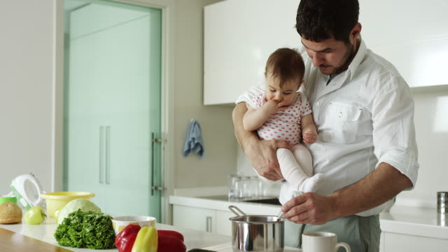 Father holding son and cooking