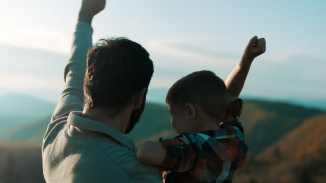 Father holding son in his arms and they raising hands up in the air on top of the mountain