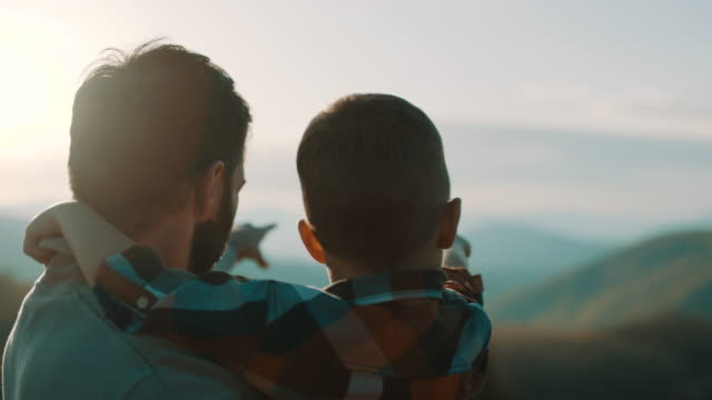 father holding son in his arms on top of the mountain - serenità video stock e b–roll