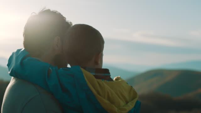 vidéos et rushes de père fils tenant dans ses bras au-dessus de la montagne - affectueux