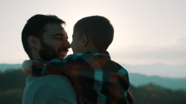 vídeos de stock e filmes b-roll de father holding son in his arms on top of the mountain - filho