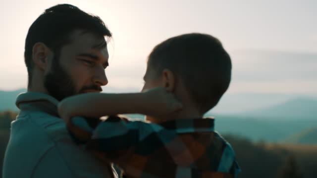 Père fils tenant dans ses bras au-dessus de la montagne