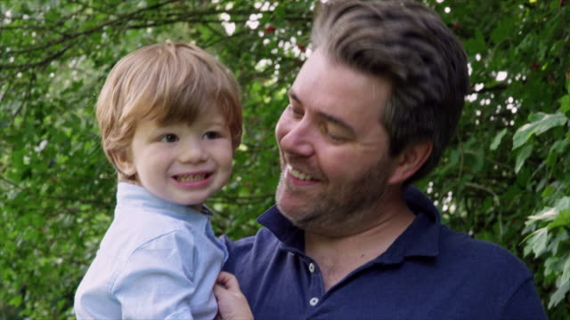 stockvideo's en b-roll-footage met father holding son - genderblend