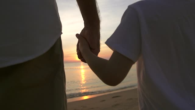 father holding the hand of his son walking on the beach at sunrise, they spend quality family time together. - son stock videos & royalty-free footage