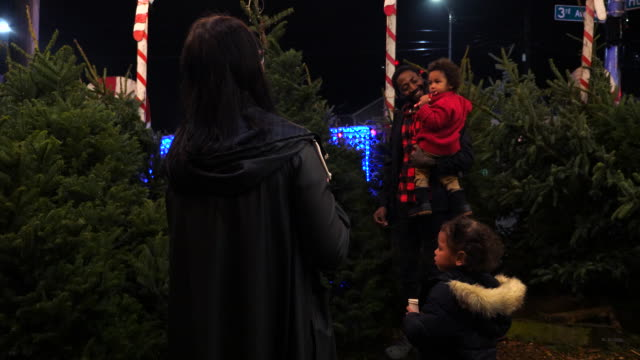 ms father holding toddler son eating candy cane while shopping for christmas tree with family - candy cane stock videos & royalty-free footage