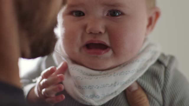 cu slo mo. father holds and comforts infant daughter as she cries. - frustration stock-videos und b-roll-filmmaterial