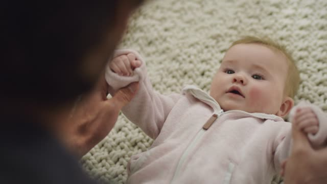 stockvideo's en b-roll-footage met cu. father holds his infant daughter's hands and moves her arms in a cute dancing motion. - vasthouden