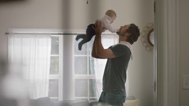 Father holds up infant daughter and kisses her forehead in sunny living room.