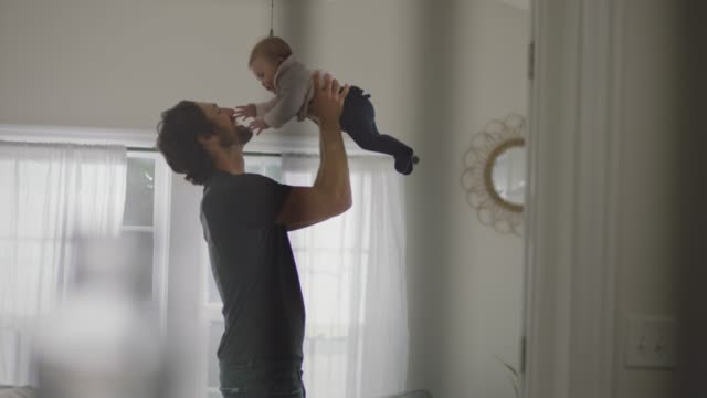slo mo. father holds up infant daughter lovingly and she reaches out to touch his face in sunny living room. - togetherness stock-videos und b-roll-filmmaterial