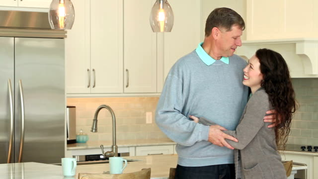 Father hugging adult daughter, standing in kitchen
