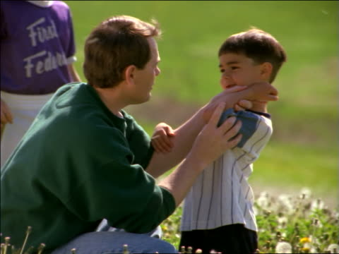 pan father hugging + comforting son in little league game  with scraped elbow - youth baseball and softball league stock videos and b-roll footage