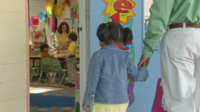 vídeos y material grabado en eventos de stock de ms father hugging daughter and waving to her outside preschool doorway as she enters classroom / san antonio, texas, usa - escuela preescolar