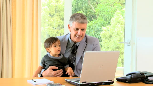 father in suit working on his laptop with child in his arms / cape town, western cape, south africa - genderblend stock videos & royalty-free footage