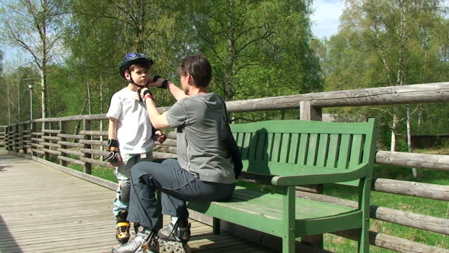 father is checking the protected young skater - sports helmet stock videos and b-roll footage