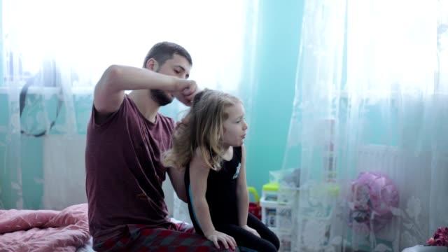 vídeos de stock e filmes b-roll de father is combing his daughter's hair. - estilo de cabelo