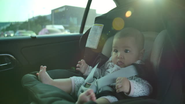 father is taking children to sit on car seat. flare light from the sunset - belt stock videos & royalty-free footage