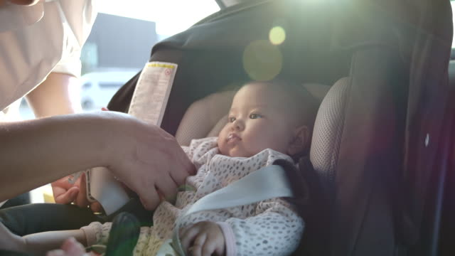 father is taking children to sit on car seat. flare light from the sunset - seat stock videos & royalty-free footage