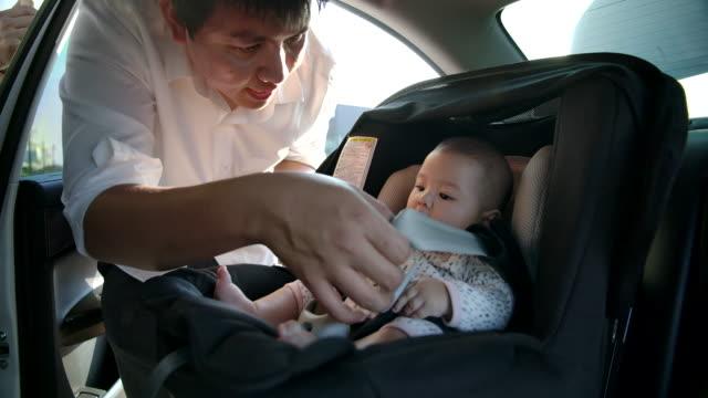 stockvideo's en b-roll-footage met vader neemt kinderen om op autostoel te zitten. flare licht van de zonsondergang - veiligheidsgordel