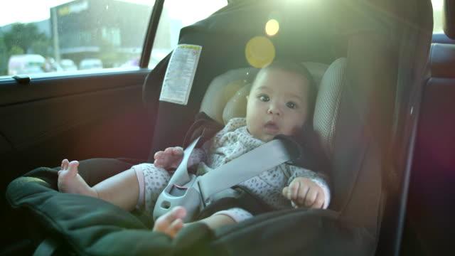 stockvideo's en b-roll-footage met vader neemt kinderen om op autostoel te zitten. flare licht van de zonsondergang - landvoertuig