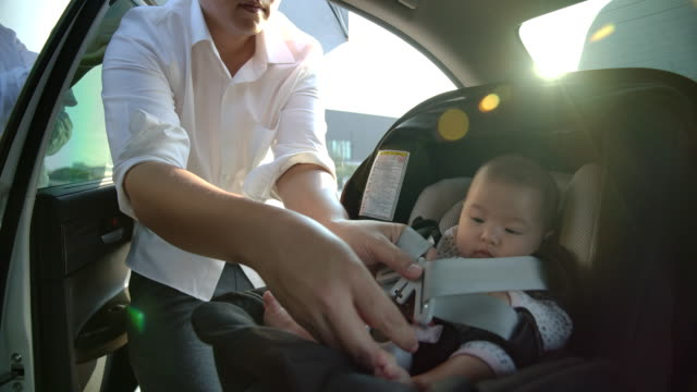 father is taking children to sit on car seat. flare light from the sunset - baby girls stock videos & royalty-free footage