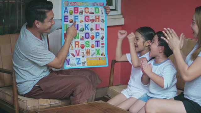 father is teaching children to reading english alphabet,slow motion - the alphabet stock videos & royalty-free footage