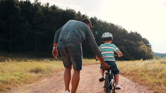 father is teaching his small son to ride bicycle in park - thoroughfare stock videos & royalty-free footage