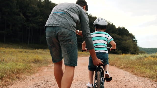 father is teaching his small son to ride bicycle in park - riding stock videos & royalty-free footage