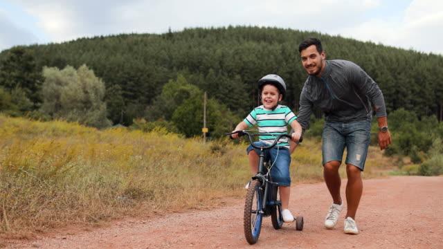 stockvideo's en b-roll-footage met vader leert zijn kleine zoon om fiets te rijden in park - zoon