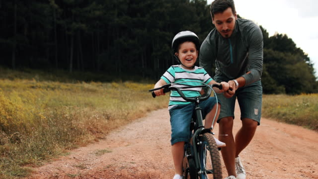 father is teaching his small son to ride bicycle in park - teaching stock videos & royalty-free footage