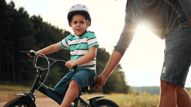 father is teaching his small son to ride bicycle in park - son stock videos & royalty-free footage