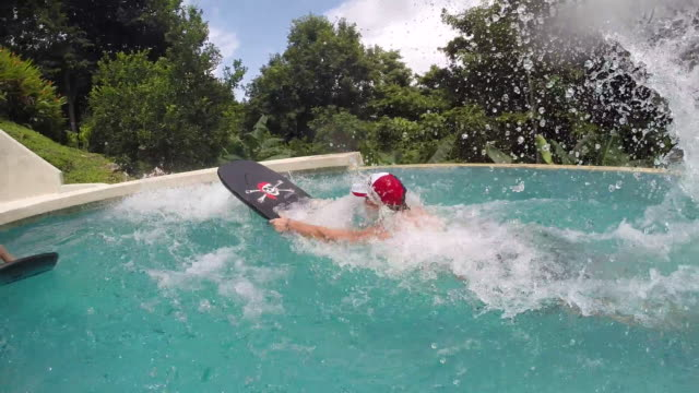 Father jumps into pool on boogie board and son is on boogie board in pool.