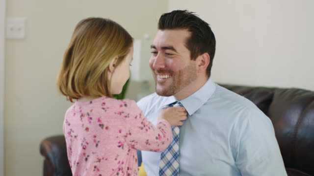 MS. Father kisses his daughter as she pulls his tie tight before he leaves for work in morning.