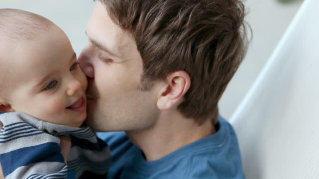 Father kissing baby son on cheek