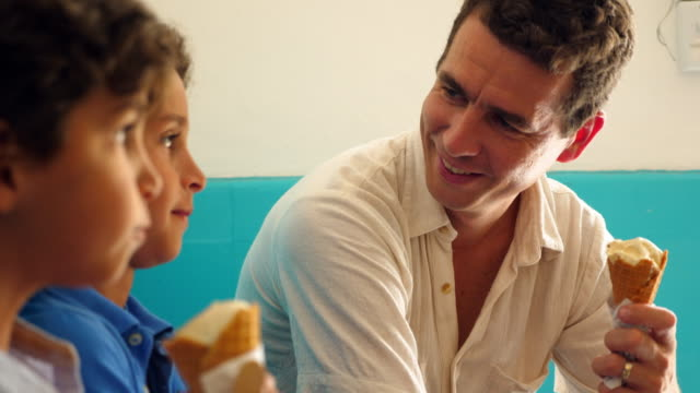 MS Father kissing young son while eating ice cream together in ice cream shop