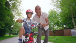 SLO MO TS Father letting go of his son learning to ride a bike and the boy takes off on his own