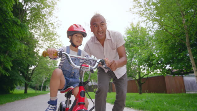 slo mo ts father letting go of his son learning to ride a bike and the boy takes off on his own - bicycle stock videos & royalty-free footage