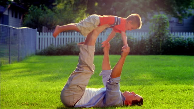 A  father lies in the grass and hoists his son above him using his hands and feet.