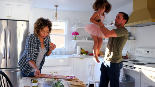 ms father lifting daughter in air while preparing dinner in kitchen with wife - vorbereitung stock-videos und b-roll-filmmaterial