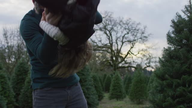 father lifting his daughter onto his shoulders - oggetto creato dall'uomo video stock e b–roll