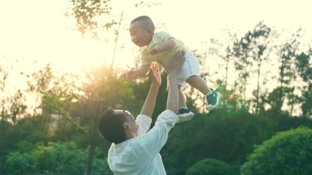 father lifting his laughing little son playfully - genderblend stock videos & royalty-free footage