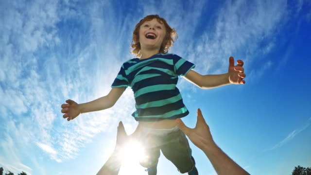 pov father lifting his laughing son into the air on a sunny day - enjoyment stock videos & royalty-free footage