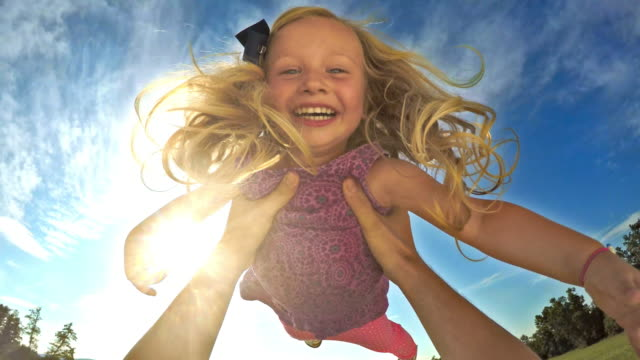 pov father lifting his smiling daughter into the air on sunny day - joy stock videos & royalty-free footage