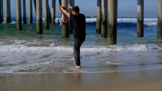father lifts son up over the water - huntington beach california stock videos and b-roll footage
