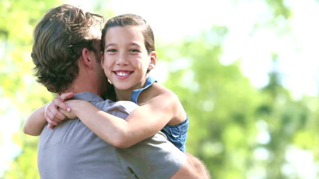 Father lifts up daughter and she smiles at the camera