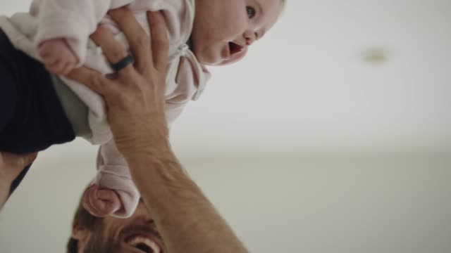 cu slo mo. father lifts up infant daughter and flies her around sunny living room. - reggere video stock e b–roll