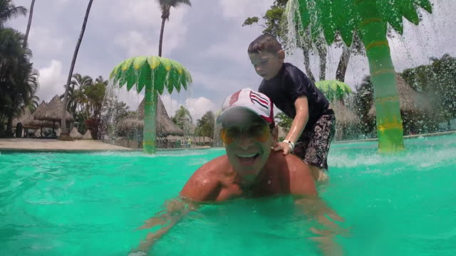 father looks into the camera as he lies in a waterpark pool and son jumps on his back and the camera submerges into the water on the father. - kelly mason videos stock videos & royalty-free footage